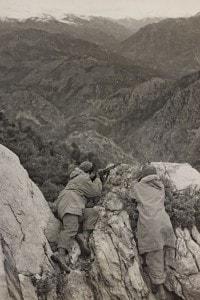 Partigiani appostati sullo sperone di una roccia durante la Seconda Guerra Mondiale.