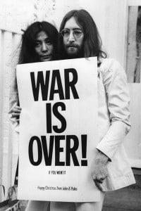 John Lennon (1940 - 1980) and Yoko Ono posano con uno slogan contro la guerra in Vietnam