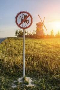 Cartello stradale che simpaticamente proibisce Don Chisciotte nei pressi di un mulino a vento