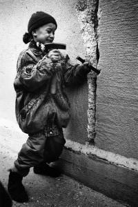 Foto di una bambina che tenta di rompere il muro dal lato di Berlino Est