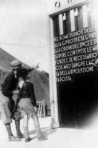 """Un soldato indica il """"giuramento fascista"""" ad un Balilla (bambino fascista)"""