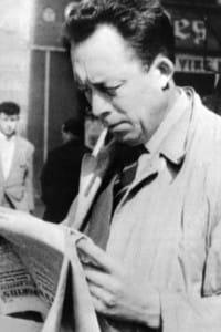 Albert Camus (1913-1960), lo scrittore francese Nobel per la letteratura mentre legge un giornale a Parigi.