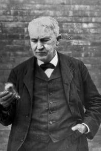 Thomas Edison tiene in mano una lampadina a incandescenza