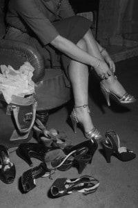 Anni '50, una donna prova delle scarpe in un negozio. La richiesta di beni di consumo secondari aumenta esponenzialmente.