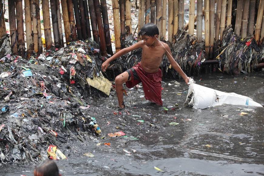 Un bambino fa il bagno tra i rifiuti a Jakarta, Indonesia