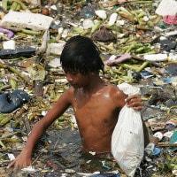 Ragazzo in mezzo ai rifiuti delle Filippine