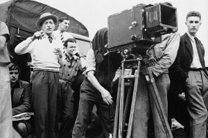 """Jean Cocteau (a sinistra con cappello) dirige una scena del suo film """"La belle et la bête"""". Francia, 1946"""