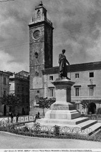 L'Aquila, Piazza Palazzo. Monumento a Sallustio e Torre del Palazzo di Giustizia