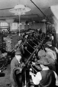 Operai su una catena di montaggio nello stabilimento Ford Motor Company a Highland Park (Michigan) che costruiscono sistemi di sterzo, 1913