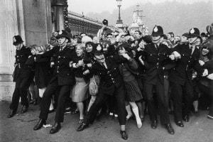 Fans in delirio fuori da Buckingham Palace, il giorno in cui i Beatles ricevono il titolo di Baronetti