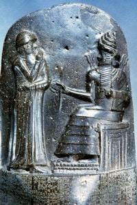 Hammurabi (in piedi) raffigurato mentre riceve le insegne reali da Shamash, dio della giustizia. Museo del Louvre