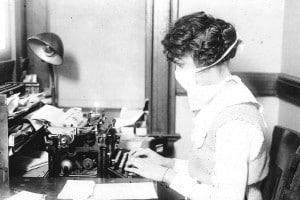 Una dattilografa indossa una mascherina durante la pandemia di influenza spagnola, 1918