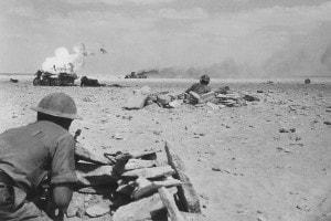1942 circa: due soldati alleati osservano due veicoli da guerra tedeschi in fiamme dopo la ritirata dell'Afrika-Korps di Rommel nel deserto nordafricano